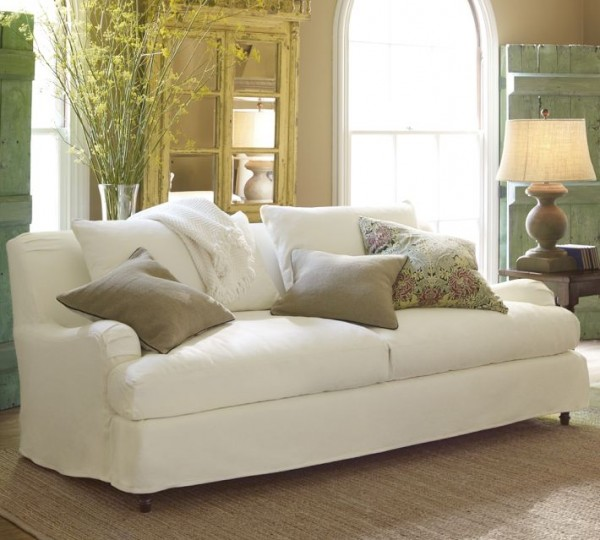 A traditional English roll arm couch with slipcovers from Pottery Barn.
