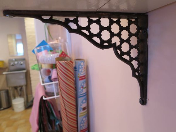 Antique iron shelf brackets add old-world charm to a new craft room