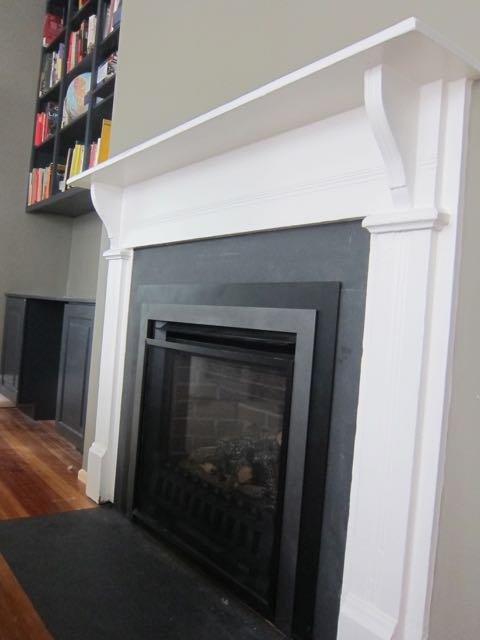 A reclaimed mantel was installed in a new living room renovation to make it look like it came with the old house