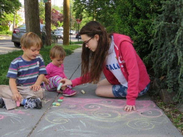 Sofia doing sidewalk drawings with Luke and Diana.