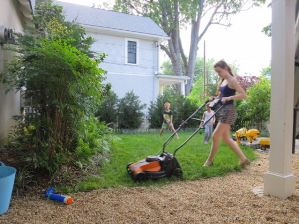 Cutting the grass with a battery-powered lawnmower.