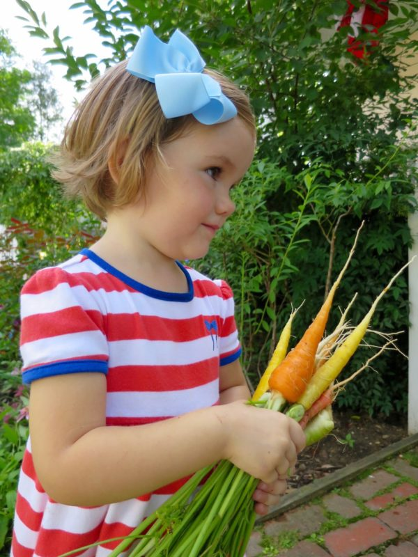 Diana holding homegrown carrots